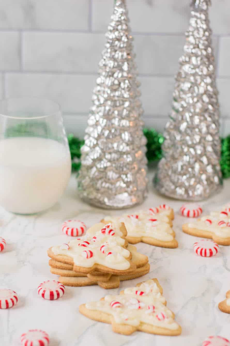 stack of peppermint sugar cookies with milk and Christmas trees in the background