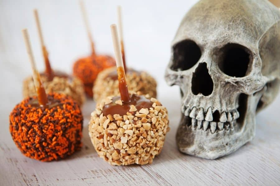 caramel apples with a skull beside them