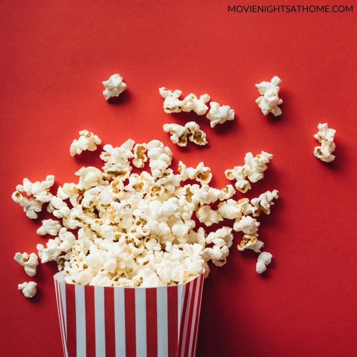 popcorn in a bucket in front of a red background