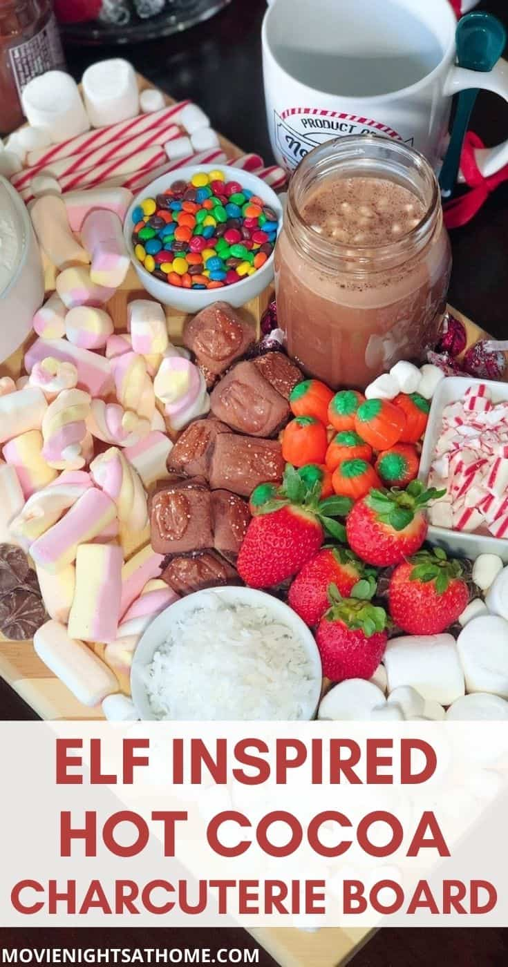 ELF hot cocoa charcuterie board with marshmallows, candy corn, candy canes, strawberries, and coconut