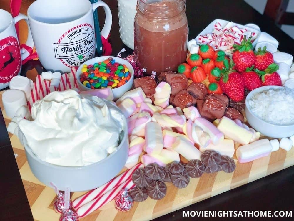 Elf Inspired Hot Chocolate Charcuterie Board with marshmallows, candy, candy corn, candy canes, coconut, and strawberries