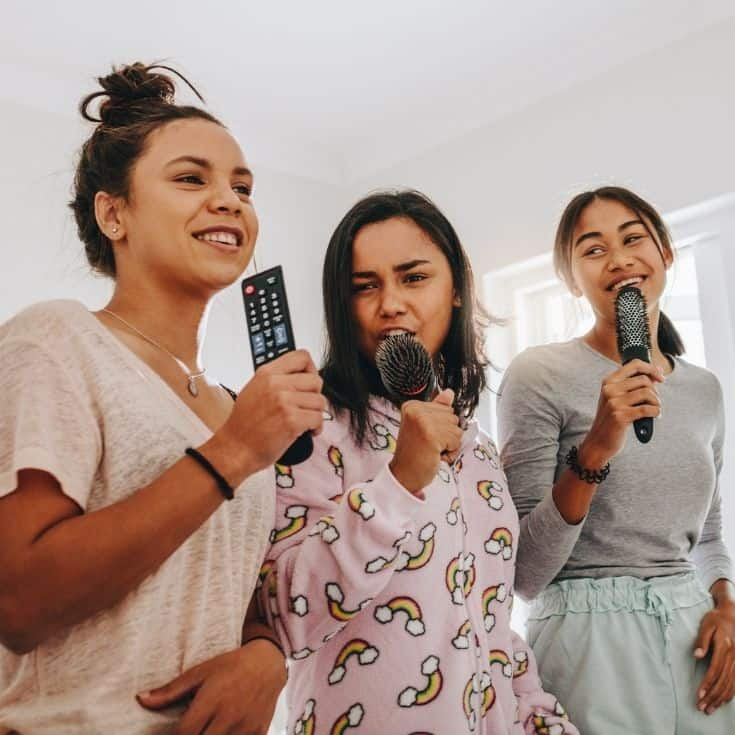 3 girls singing into a hair brush - karaoke is just one of our slumber party ideas