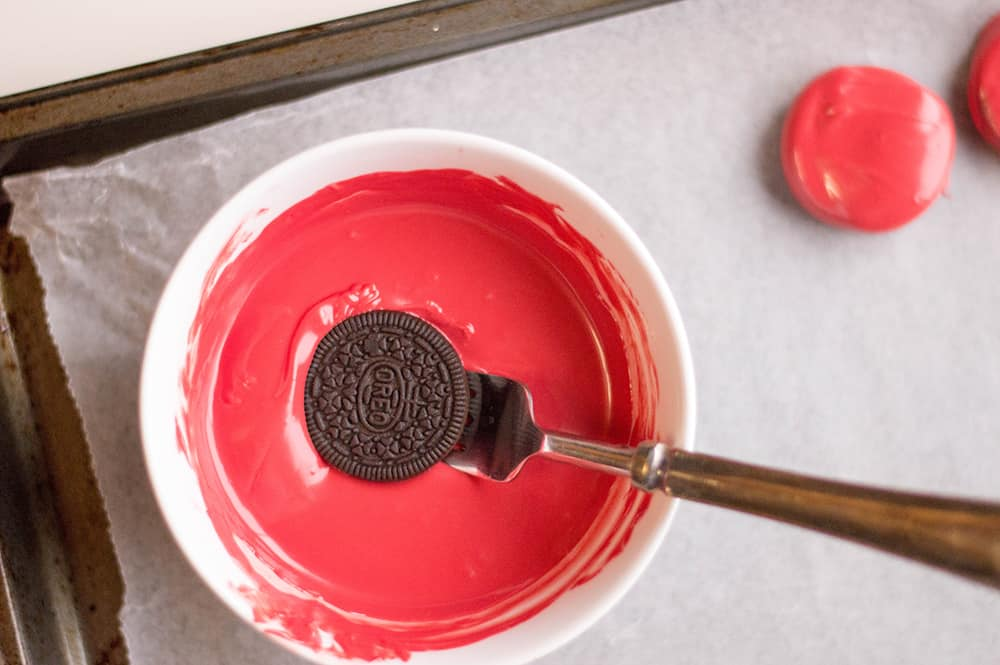 dipping the oreo into the melted candy melts