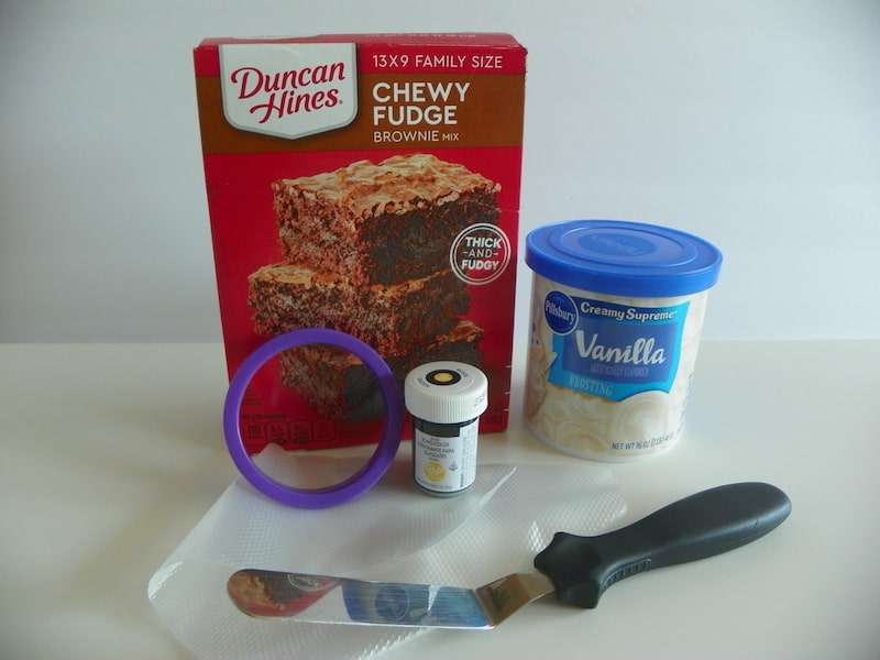 brownie mix, frosting, cooking cutter, spreader, and black food coloring