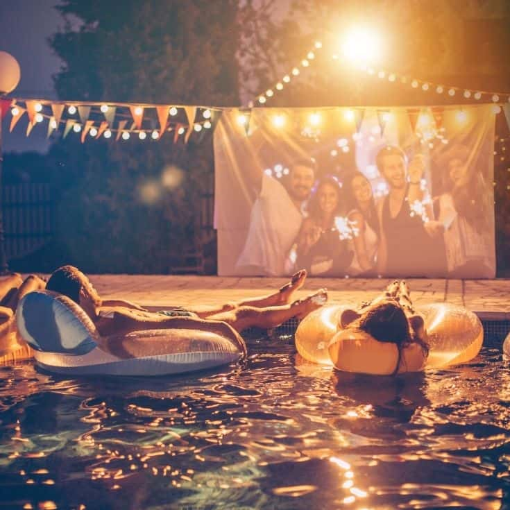 friends sitting in the pool on floats watching a movie