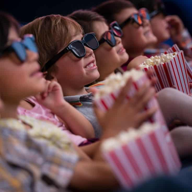 4 kids watching a movie with 3D glasses on and eating popcorn